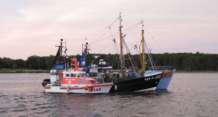 """Das Seenotrettungsboot """"Heinz Orth"""" der DGzRS hat Feuerwehrleute auf den Fischkutter """"Einheit"""" übergeben, um einen Schwelbrand zu bekämpfen. Längsseits der """"Einheit"""" liegt außerdem der Kutter """"Bergen"""" (hi.) - Foto: DGzRS/Die Seenotretter"""